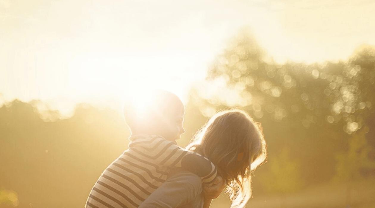 Enfant sur le dos d'une adolescente, soleil en arrière plan