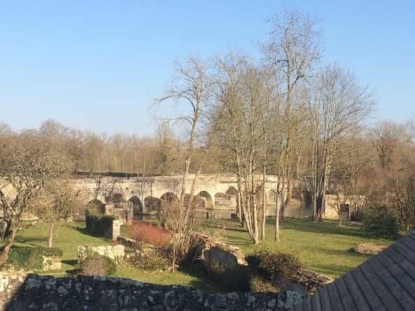 View of the bridge in Grez-sur-Loing, blue sky, leafless trees.