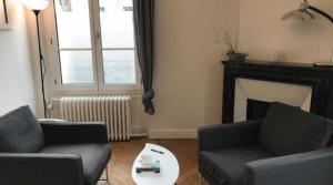 Bureau avec 2 fauteuils, une grande fenêtre et une cheminée.