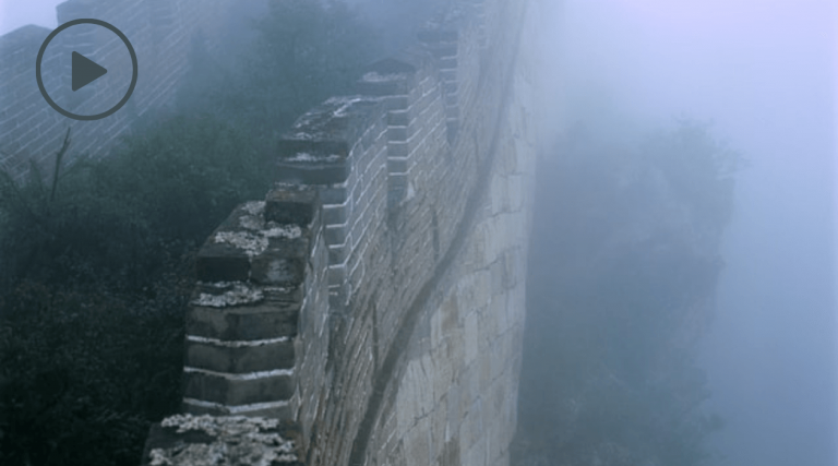 Like hidden barriers to your happiness, a tall stone wall stands in the fog